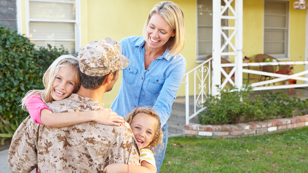 Happy family welcoming home soldier on front lawn